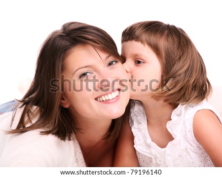 A portrait of a little girl kissing her mom over white background - stock photo