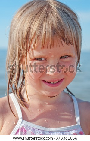 A portrait of a little girl with drops of water on her face