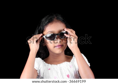 A portrait of a little Indian girl trying to be stylish by wearing trendy sunglasses, on black studio background.