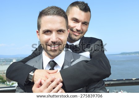A Portrait of a loving gay male couple on their wedding day with sky on the back.  - stock photo