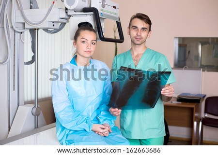 A portrait of a male doctor and a nurse looking at x-ray in a clinic medical lab - stock photo