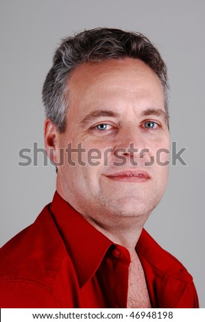 A portrait of a middle age man with light gray hair, closeup in a red shirt in the studio, for light gray background.