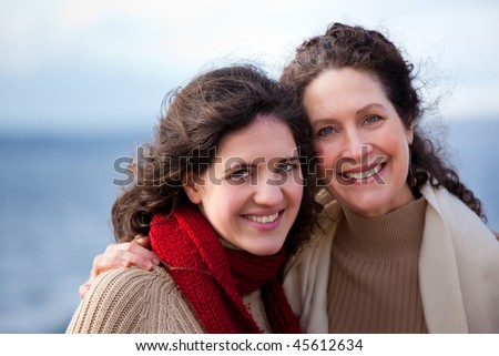 A portrait of a mother and her daughter on the beach - stock photo