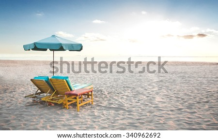 A portrait of a pair of beach chair with umbrella in a seashore - stock photo