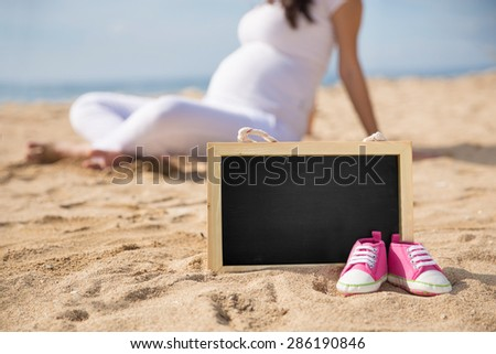 A portrait of a pair of Pink Toddler sneakers and mini chalk board on the sand with pregnant woman on the background - stock photo