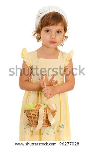 A portrait of a pensive little girl with the Easter basket; isolated on the white background