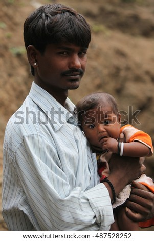 A portrait of a  poor Indian worker holding his baby in his arms