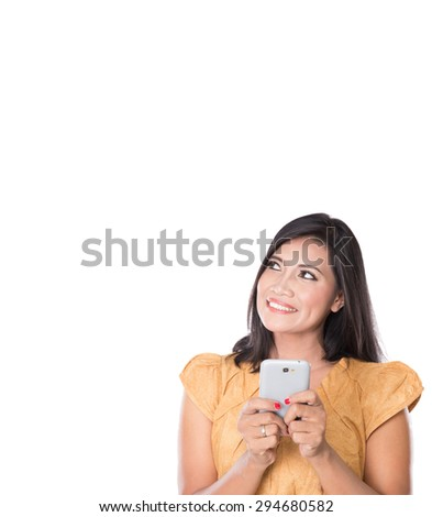 A portrait of a pretty Asian Woman, text on her cellphone and looking up to copyspace - stock photo