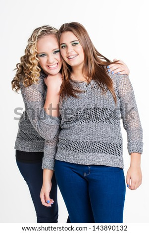 a portrait of a pretty blond caucasian girl hugging her best friend with brunette hair from behind with both girls smiling happily and wearing matching gray jerseys - stock photo