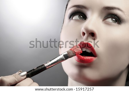 a portrait of a pretty girl with brush and paint - stock photo
