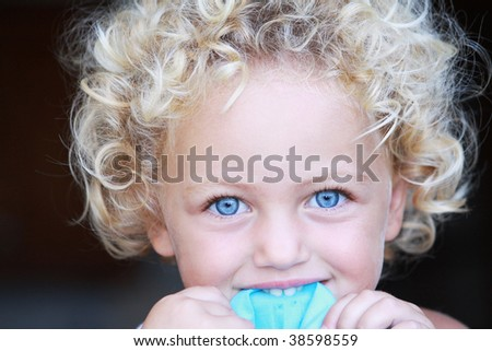 a portrait of a pretty young child with fair hair and blue eyes - stock photo