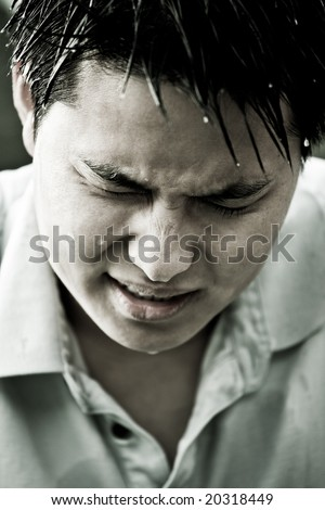 A portrait of a sad and depressed young asian man - stock photo