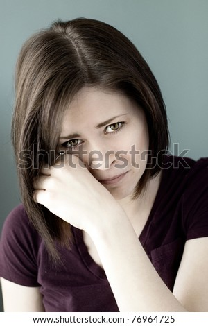 A portrait of a sad young woman crying and wiping her eyes. - stock photo