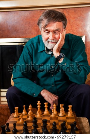 A portrait of a senior caucasian man playing chess - stock photo