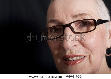 A portrait of a serious looking senior woman with short white hair, heavy dark rimmed glasses and light makeup on. - stock photo