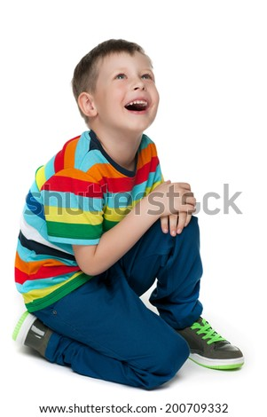 A portrait of a sitting curious little boy on the white background - stock photo