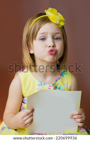 A portrait of a smiling cute little girl in a dress with empty blank in hands, isolated on brown, close up. Holidays concept. Invitation. Funny kids. - stock photo