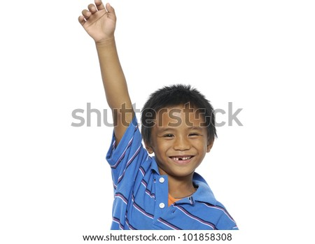 A portrait of a smiling little boy holding his hand up