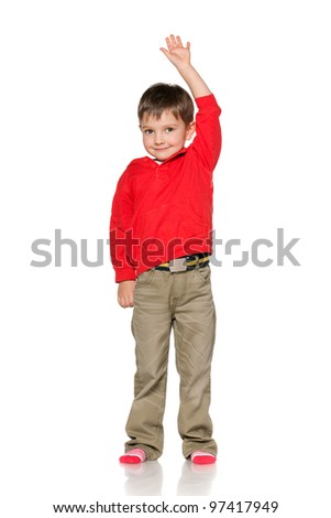 A portrait of a smiling little boy holding his hand up; isolated on the white background - stock photo
