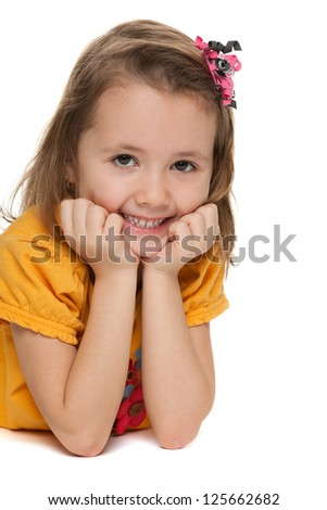 A portrait of a smiling little girl in a yellow shirt; on the white background