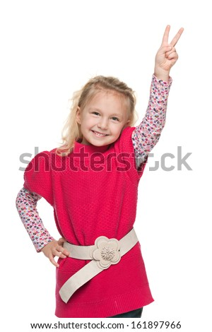 A portrait of a smiling little girl shows victory sign on the white background
