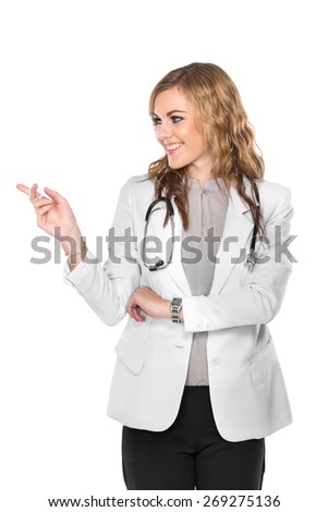 A portrait of a smiling young beautiful female doctor showing blank area for sign or copyspace, isolated over white background - stock photo