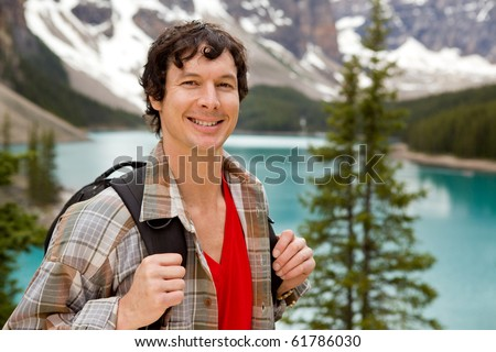 A portrait of a smiling young male at Lake Moraine, Alberta, Canada - stock photo