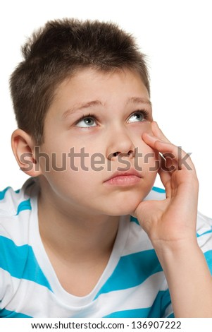 A portrait of a thoughtful boy looking up; on the white background - stock photo