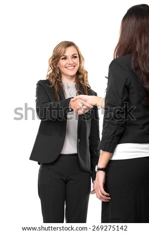 A portrait of a two young businesswoman making a deal and shaking hands isolated on a white background - stock photo
