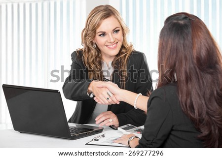 A portrait of a Two young businesswoman shaking hand - stock photo