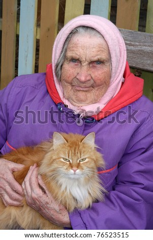 A portrait of a very old woman, 91 years old near his house, has control over a red cat - stock photo