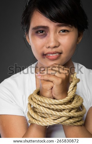 A portrait of a woman with hands tied up with rope being abused,   struggle, terrified,  and threaten from domestic violence and abuse - stock photo