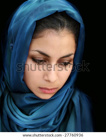 A portrait of a young arab woman in a blue scarf - stock photo