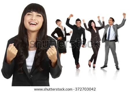 A portrait of a young asian businesswoman with her team behind, make a success gesture. isolated in white background - stock photo