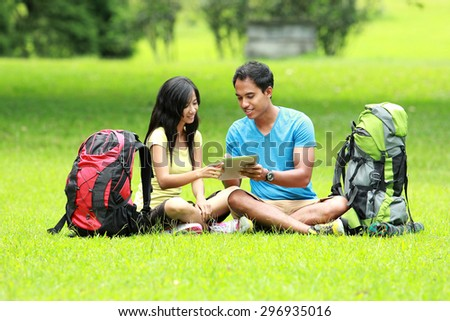 A portrait of a young asian couple sitting on the park looking a tablet pc - stock photo