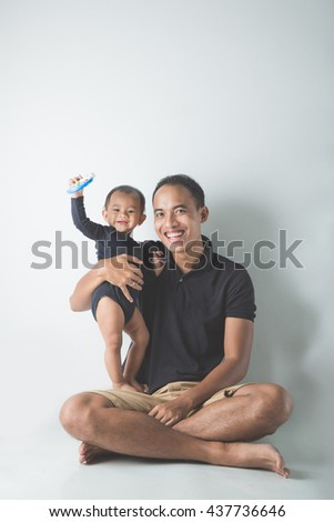 A portrait of a Young Asian father holding his adorable baby on white background - stock photo