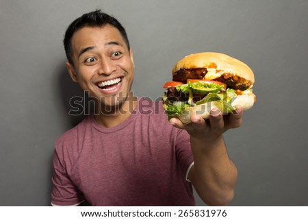 A portrait of a young asian man happy when get a big burger - stock photo