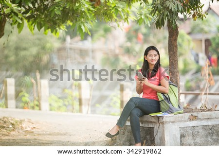 A portrait of a young Asian student sitting outdoor, holding a cellphone - stock photo