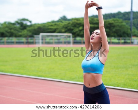 A portrait of a young asian woman doing exercise outdoor in day light, stretching. - stock photo