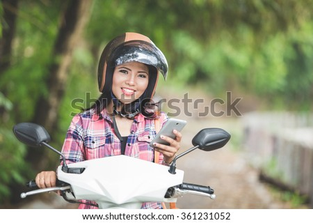 A portrait of a young asian woman holding a cellphone while sitting on a motorcycle in a park - stock photo