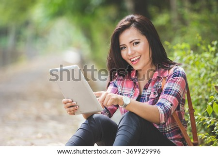 A portrait of a young asian woman holding a tablet pc while sitting on the park