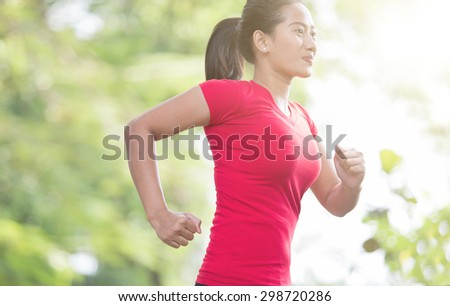 A portrait of a young asian woman jogging at the park - stock photo