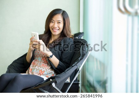 A portrait of a young asian woman sit and use her smart phone - stock photo