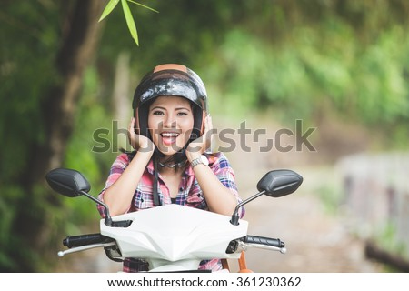 A portrait of a young asian woman sitting in a motorcycle on a park, both hand holding helmet - stock photo