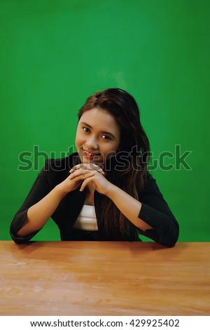 A portrait of a young asian woman with smiles expression while sitting - green screen for compositing