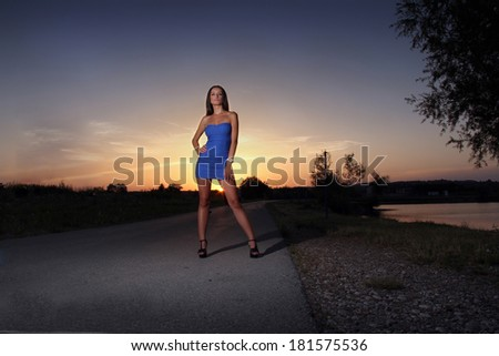 A portrait of a young beautiful woman, on a sunset background.