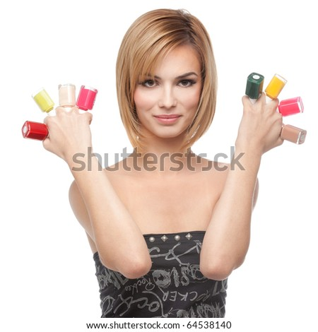 a portrait of a young blonde woman, smiling, holding both her hands up, next to her face and showing eight bottles of colored nail polish. - stock photo