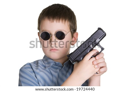 A portrait of a young boy holding a handgun on a white background. Depth of field with focus on gun. - stock photo