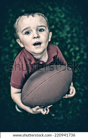 A portrait of a young boy posing with a football outside holding it in his hands looking up at the camera.  Filtered for a retro, vintage look.  - stock photo