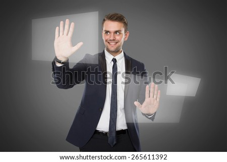 A portrait of a young businessman push against virtual screen - stock photo